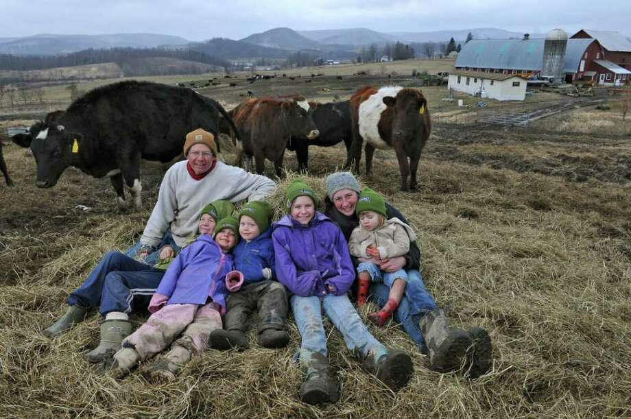 Paul and Phyllis Van Amburgh, second from right, with their children, from left to right, Vincent, 10, Maggy, 6, Oliver, 4, Grace, 11 and Ruby, 2, on their Dharma Lea farm on Thursday Feb. 2, 2012 in Sharon Springs, NY.   Their organic dairy and beef farm is the subject of a documentary.  (Philip Kamrass / Times Union ) Photo: Philip Kamrass / 00016309A