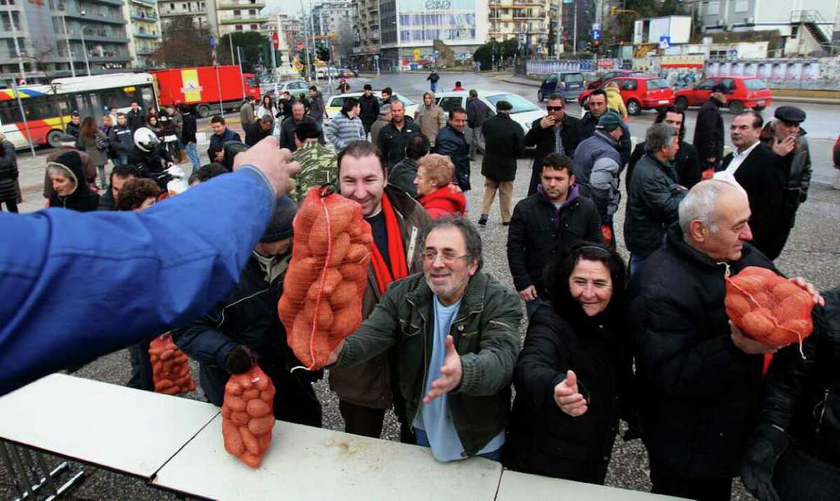 People receive agricultural produce offered for free by protesting farmers during a farmers' protest in the northern port city of Thessaloniki, Greece on Saturday, Feb. 4 2012. Farmers from the Greek province of Central Macedonia were doling out 6-kilo potato bags to members of the public in the center of the town, outside a farming exhibition in protest, they said, at middlemen forcing them to sell their produce at very low prices. (AP Photo/Nikolas Giakoumidis)