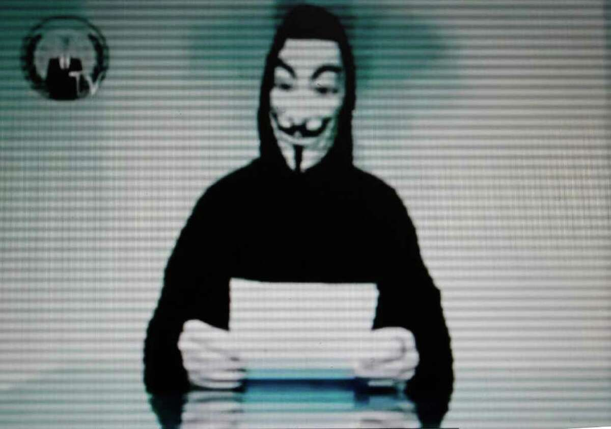 This image taken from a video posted by Internet hackers on the Greek Justice Ministry web site on Friday, Feb. 3, 2012, shows a figure in a Guy Fawkes mask reading a statement. Greek and Cypriot hackers from the