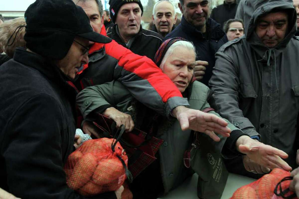 People receive agricultural produce offered for free by protesting farmers during a farmers' protest in the northern port city of Thessaloniki, Greece on Saturday, Feb. 04 2012. Farmers from the Greek province of Central Macedonia were doling out 6-kilo potato bags to members of the public in the center of the town, outside a farming exhibition in protest, they said, at middlemen forcing them to sell their produce at very low prices. (AP Photo/Nikolas Giakoumidis)