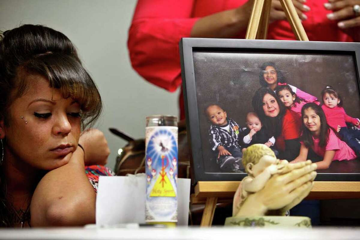 Sabrina Benitez, the mother of Joshua Davis Jr., sits next to a photograph of her mother, Natalie Vargas, with Vargas' daughter and grandchildren including Joshua (far left in photograph), just two weeks before he disappeared, during a event marking the one-year anniversary of his disappearance in New Braunfels at the Heidi Search Center in San Antonio on Saturday, Feb. 4, 2012.