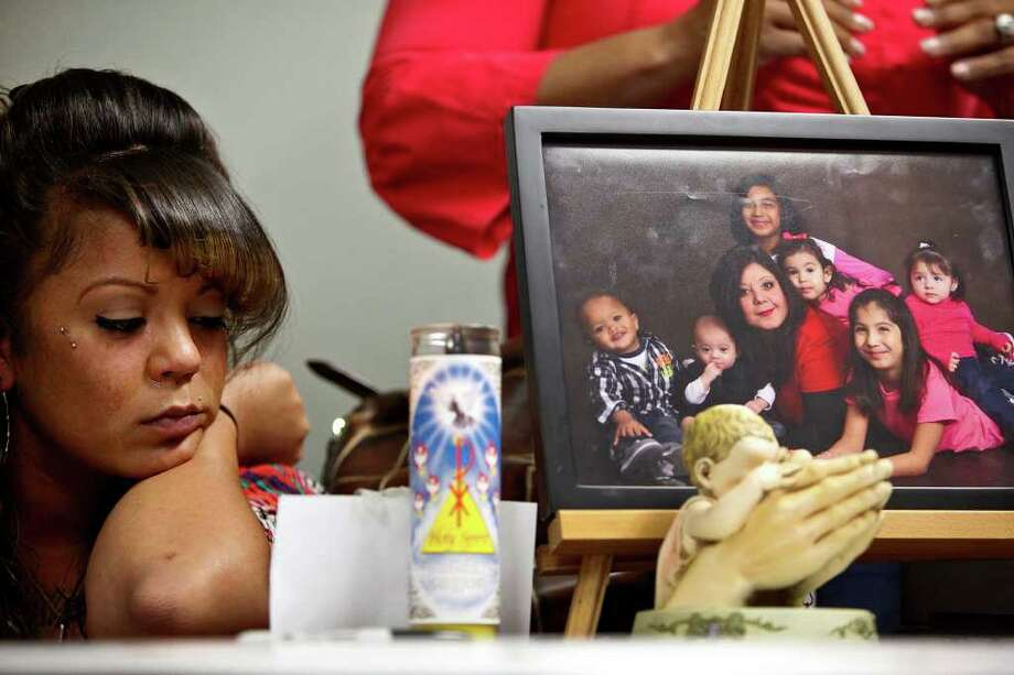 Sabrina Benitez, the mother of Joshua Davis Jr., sits next to a photograph of her mother, Natalie Vargas, with Vargas' daughter and grandchildren including Joshua (far left in photograph), just two weeks before he disappeared, during a event marking the one-year anniversary of his disappearance in New Braunfels at the Heidi Search Center in San Antonio on Saturday, Feb. 4, 2012. Photo: Lisa Krantz, San Antonio Express-News / @2012 SAN ANTONIO EXPRESS-NEWS