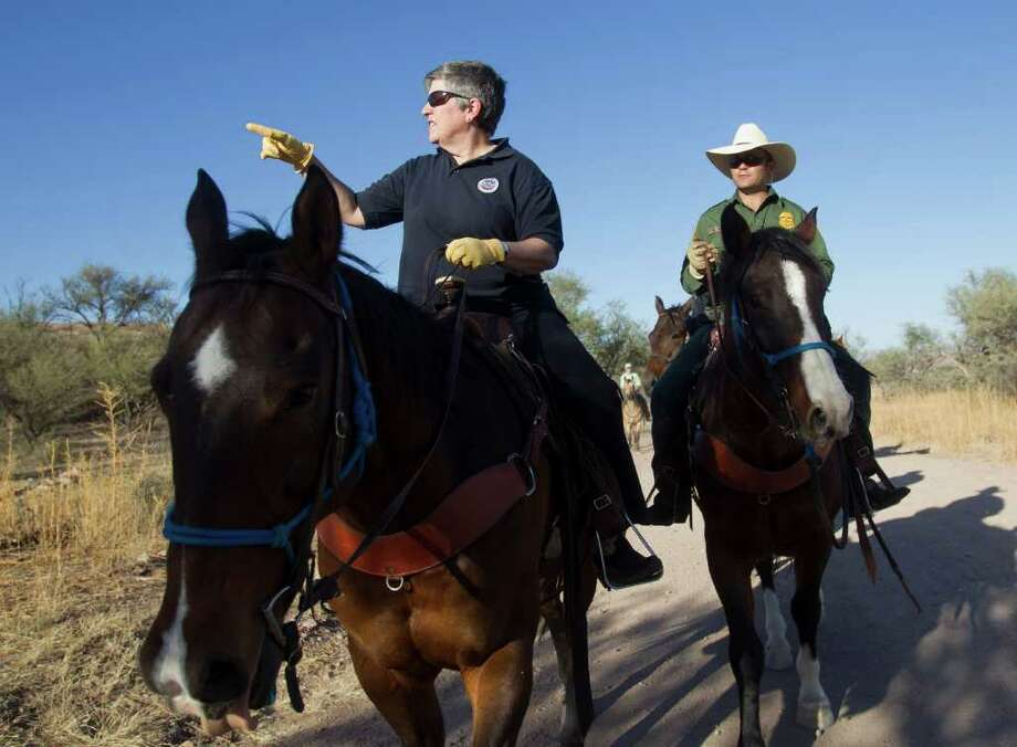 "FILE - In this Oct. 30, 2011, file photo Homeland Security Secretary Janet Napolitano, left, tours the U.S.-Mexico border with Border Patrol agent Steve Venditouli in the Coronado National Forest near Nogales, Ariz. Most illegal border crossers are apprehended along the 2,000-mile long Mexican border in California, Arizona, New Mexico, and Texas. Since the 2006 budget year, the U.S. Customs and Border Patrol has spent more than $1.4 billion on what is described as ""administrative uncontrollable overtime,"" according to the data provided by the Border Patrol. In practical terms, agents average two hours a day in overtime. (AP Photo/The Arizona Republic, Michael Chow)  MARICOPA COUNTY OUT; MAGS OUT; NO SALES Photo: Michael Chow"