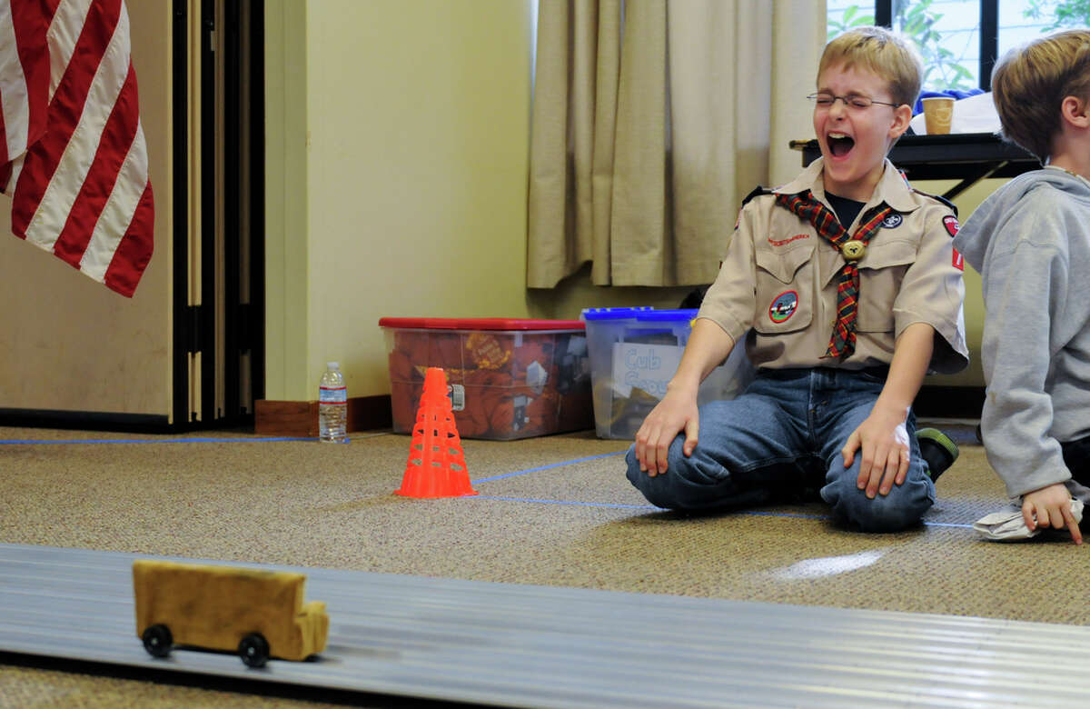Scout Anders Charlton laughs as a car comes to a stop on the track during the Queen Anne Cub Scouts' annual Pinewood Derby at Bethany Presbyterian Church in Seattle on Saturday, Feb. 4, 2012. The derby is a chance for scouts, who were each given a block of wood to carve, to exercise their visual and aerodynamic design skills with help from family members. The Queen Anne Cub Scouts have been holding the derby since at least 1988.