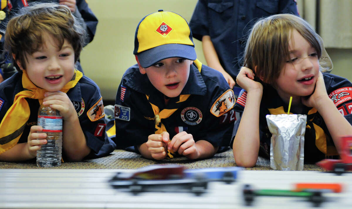 Left to right: Sam Sikora, Liam McFerin and Hudson Brown, all 7, watch their cars race down a 30-foot track during the Queen Anne Cub Scouts' annual Pinewood Derby at Bethany Presbyterian Church in Seattle on Saturday, Feb. 4, 2012. The derby is a chance for scouts, who were each given a block of wood to carve, to exercise their visual and aerodynamic design skills with help from family members. The Queen Anne Cub Scouts have been holding the derby since at least 1988.