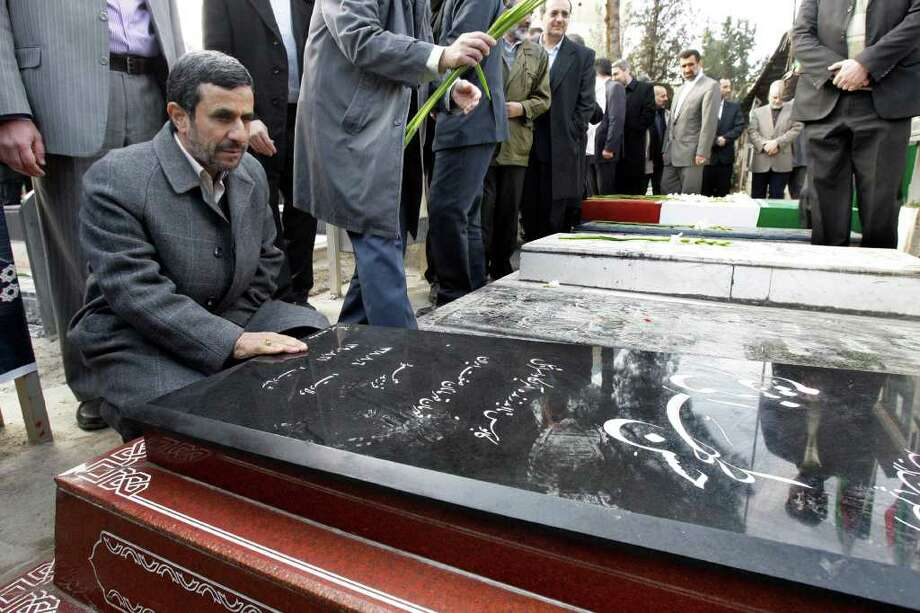 Iranian President Mahmoud Ahmadinejad, prays at the grave of Gen. Hasan Tehrani Moghaddam, a Revolutionary Guard commander, who was in charge of the country's missile program and was killed in an explosion at an ammunition depot in November 2011, in a ceremony commemorating 33rd anniversary of Iran's 1979 Islamic Revolution, at the Behesht-e- Zahra cemetery, just outside Tehran, Iran, Saturday, Feb. 4, 2012. (AP Photo/Vahid Salemi) Photo: Vahid Salemi / AP