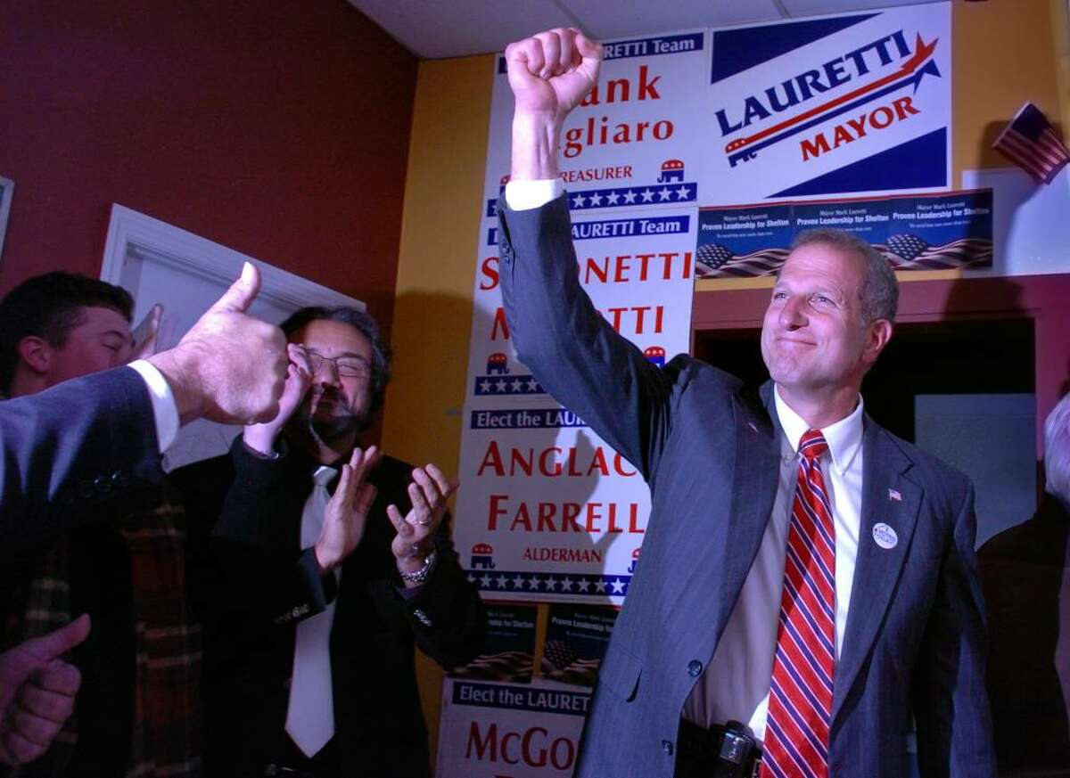 Shelton Mayor Mark A. Lauretti raises his fist in victory Tuesday at Republican headquarters after being re-elected to office.