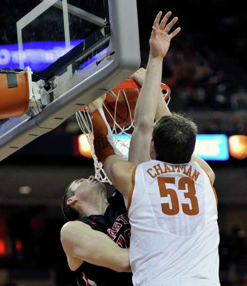 Texas center Clint Chapman, right, dunks the ball against Texas Tech forward Robert Lewandowski, left, during the second half of an NCAA college basketball game on Saturday, Feb. 4, 2012, in Austin, Texas. Chapman led all scorers with 20 points. Texas won 74-57. Photo: AP