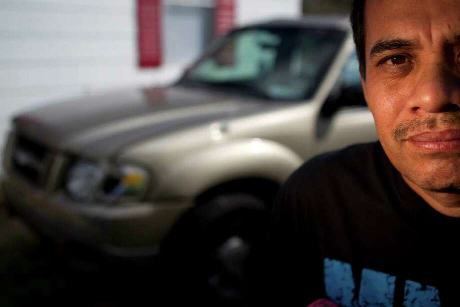 Miguel Rodriguez stands next to the bullet-scarred SUV he was repairing the night he was shot outside his north Houston home. Photo: Johnny Hanson / © 2012  Houston Chronicle