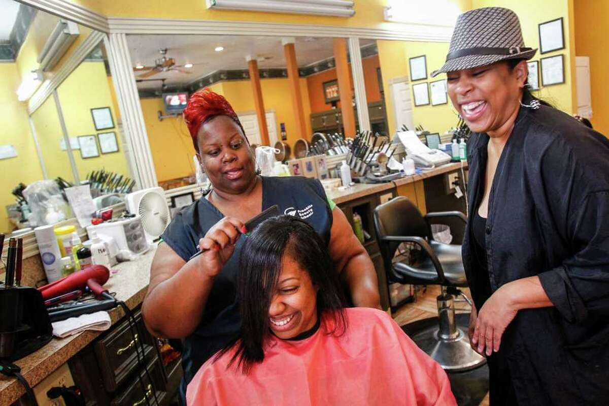 """Rochelle Bell gets her hair done by Tonja Williams as Theresa Taplin chimes in at W's Hair Factory. The salon is in one of the city's """"food desert"""" areas."""