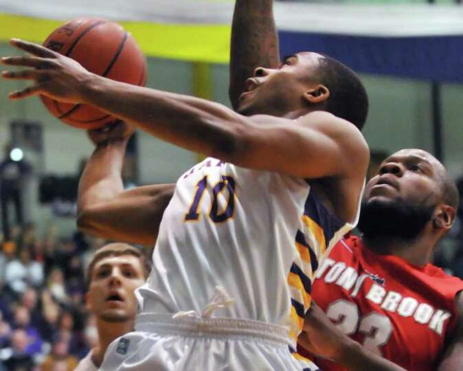 UAlbany's. #10 Mike Black crashes through Stony Brook defenders to reach the basket during Saturday'
