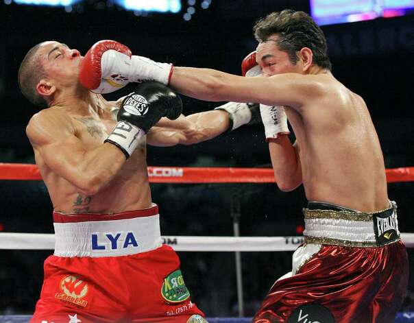 Wilfredo Vazquez, Jr.  (left) and Nonito Donaire exchange punches during the fifth round of their WBO junior featherweight title fight Saturday Feb. 4, 2012 at the Alamodome. Donaire  won the fight. Photo: EDWARD A. ORNELAS, Express-News / © SAN ANTONIO EXPRESS-NEWS (NFS)
