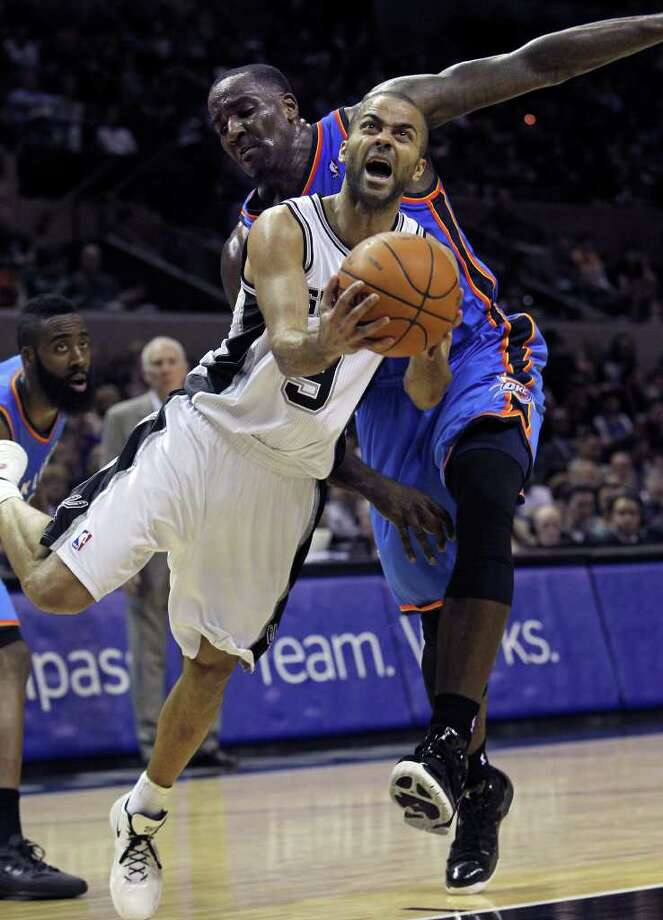 Spurs guard Tony Parker twists under Kendricks Perkins for a bucket in the first half as the San Antonio Spurs play the Oklahoma City Thunder at the AT&T Center  on February 4, 2012 Tom Reel/ San Antonio Express-News Photo: TOM REEL, Express-News / San Antonio Express-News
