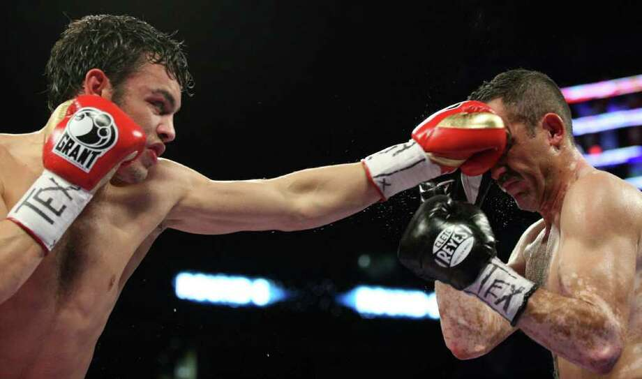 "Julio Cesar Chavez Jr. (left) lands a punch on Marco Antonio Rubio during Saturday night's ""Welcome to the Future"" fight card at the Alamodome. Chavez remained unbeaten at 45-0-1 and kept his title despite reports of a recent arrest and talk of training ""mistakes."" Photo: Express-News"