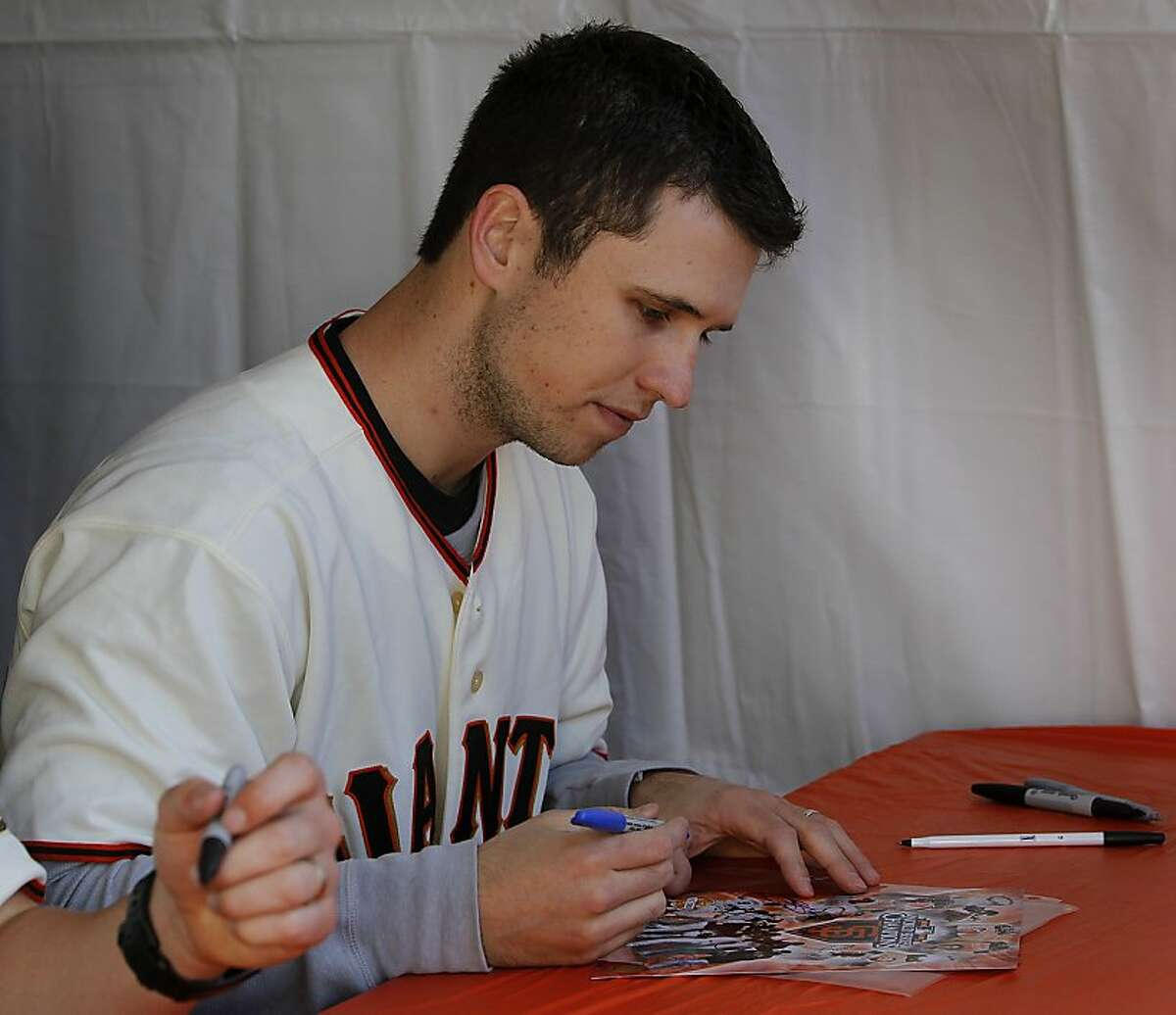 Catcher Buster Posey autographs memorabilia for fans at the annual Giants FanFest at AT&T Park in San Francisco, Calif. on Saturday, Feb. 4, 2012.
