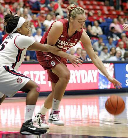 Stanford's Joslyn Tinkle, center, drives through the attempted defense by Arizona's Reiko Thomas, left, during the second half of an NCAA college basketball game at McKale Center in Tucson, Ariz., Saturday, Feb. 4, 2012. Stanford won 91-51. (AP Photo/John Miller) Photo: John Miller, Associated Press