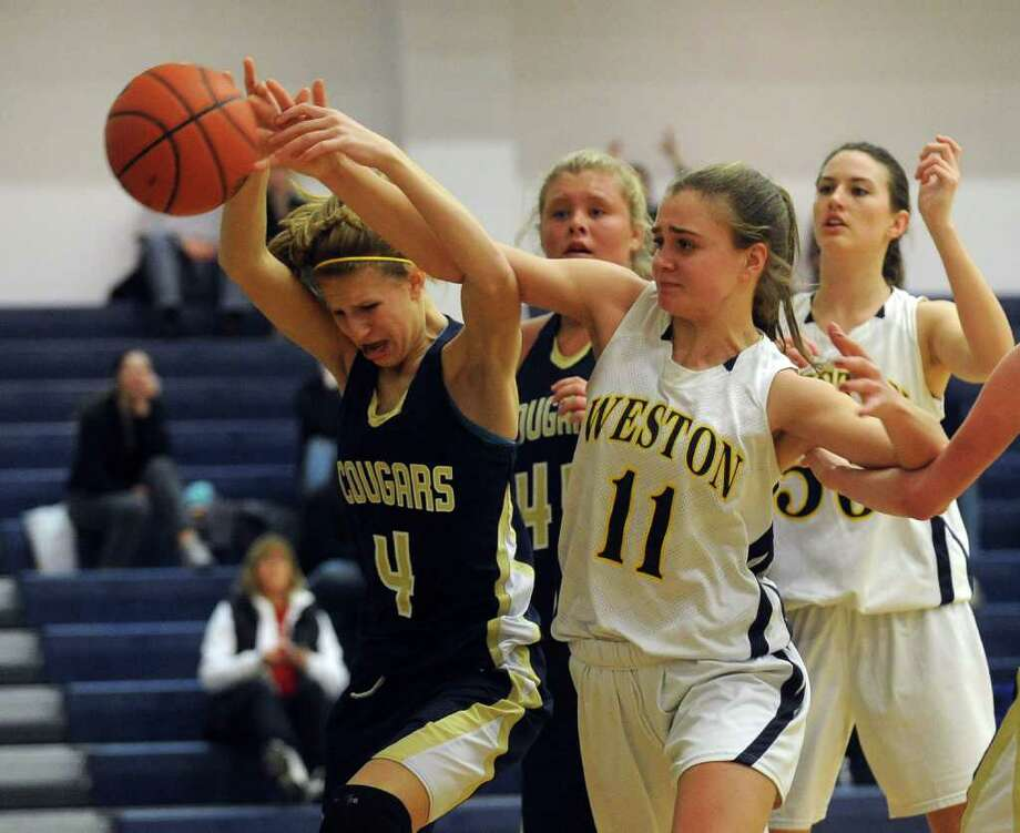 Weston's #11 Rosemary Martin and Haddam Killingworth's #4 Kiley Anderson struggle for control of a rebound, during girls basketball action in Weston, Conn. on Saturday February 4, 2012. Photo: Christian Abraham / Connecticut Post