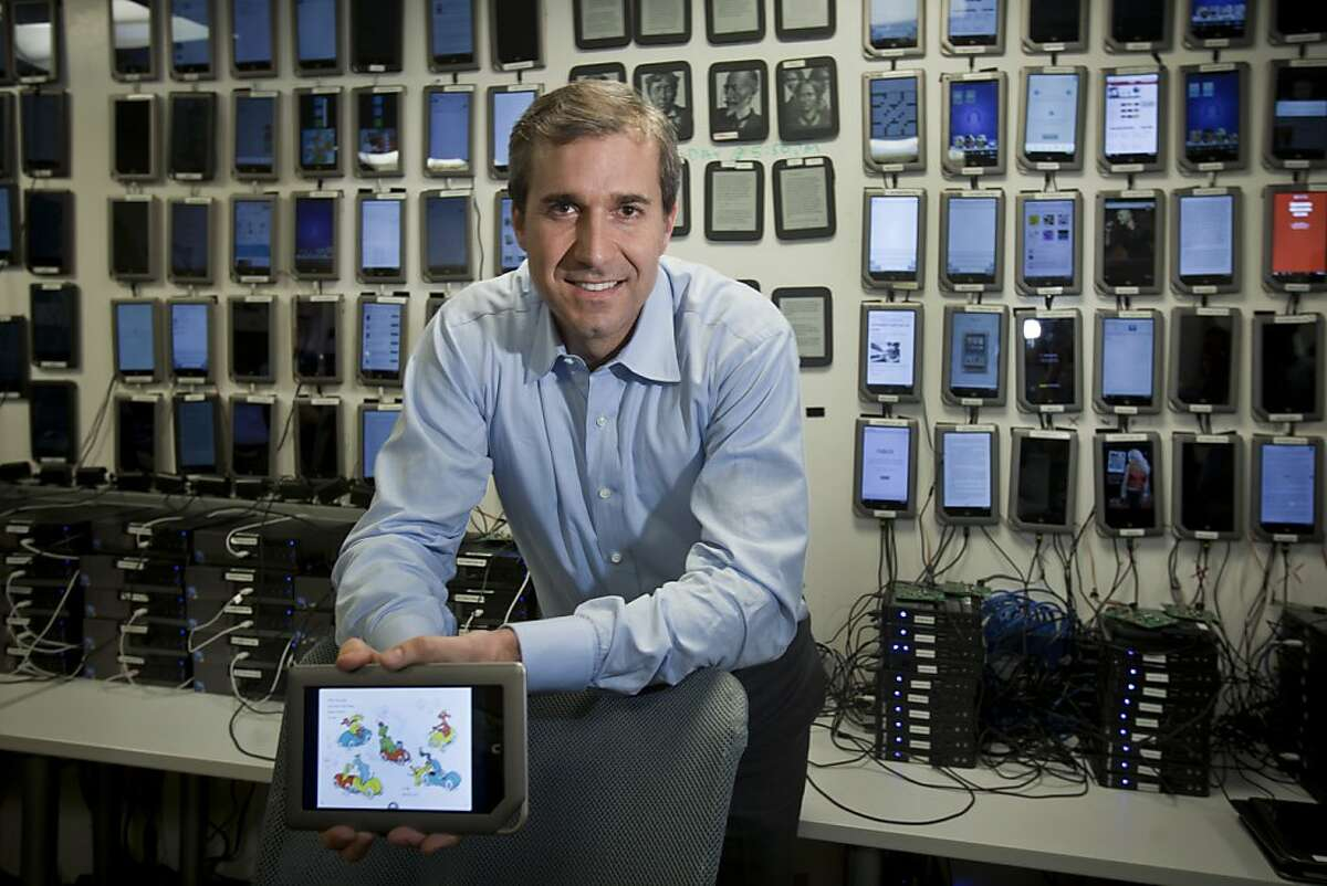 William Lynch, chief executive of Barnes & Noble, with a wall full of e-readers at a company site, where 300 employees are aiming to build the company's digital side, in Palo Alto, Calif., Jan. 24, 2012. Barnes & Noble, once viewed as the brutal capitalist of the book trade, isn't expected to disappear overnight, but there is worry that it might slowly wither as readers embrace e-books. (Peter DaSilva/The New York Times) -- PHOTO MOVED IN ADVANCE AND NOT FOR USE - ONLINE OR IN PRINT - BEFORE JAN. 29, 2012.