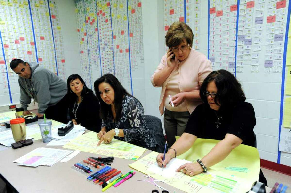 Roosevelt Elementary School principal Pamela Reece, second from right, converses with third grade teachers, from left, Isaac Gomez, Melissa Castillo, Ernestina Mendez and Star Hays in the school's War Room on Jan. 17, 2012.