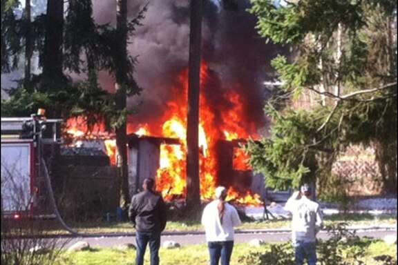 Flames pour from the home of Josh Powell after the afternoon explosion on Sunday, Feb. 5, 2012.