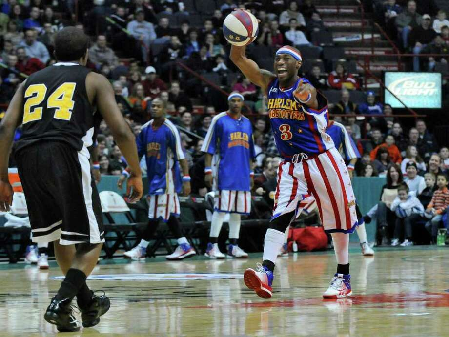 "Harlem Globetrotter ""Firefly,"", aka Siena graduate Tay Fisher, brings the ball upcourt as he entertains the crowd at the Times Union Center during a game on Sunday Feb. 5, 2012 in Albany, NY.    (Philip Kamrass / Times Union ) Photo: Philip Kamrass / 00016336A"