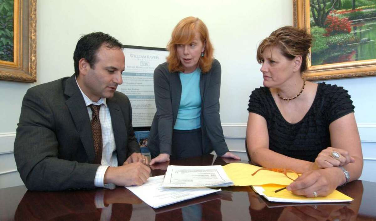 Chris Ware Staff Photographer. From left, Attorney Joseph Romanello, Short Sales Specialist Denise Marr and Abric Group representative Jeanne Abric talk at William Raveis Real Estate in Newtown, CT August 6, 2009.
