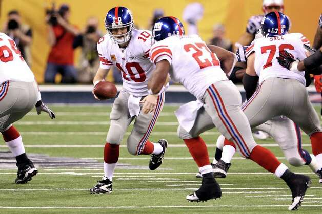 INDIANAPOLIS, IN - FEBRUARY 05:  Quarterback Eli Manning #10 of the New York Giants looks to hand off the ball to runningback Brandon Jacobs #27 in the first quarter against the New England Patriots during Super Bowl XLVI at Lucas Oil Stadium on February 5, 2012 in Indianapolis, Indiana. Photo: Andy Lyons, Getty Images / 2012 Getty Images