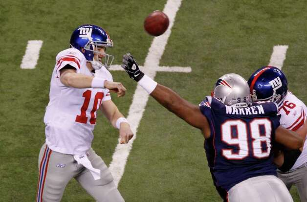 INDIANAPOLIS, IN - FEBRUARY 05:  Quarterback Eli Manning #10 of the New York Giants drops back to pass as he is pressured by Gerard Warren #98 of the New England Patriots during the first quarter against the New England Patriots during Super Bowl XLVI at Lucas Oil Stadium on February 5, 2012 in Indianapolis, Indiana. Photo: Gregory Shamus, Getty Images / 2012 Getty Images