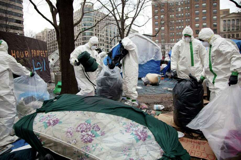 Workers in protective gear remove tents, camping gear and debris left by Occupy DC protesters in McPherson Square, Sunday, Feb. 5, 2012, in Washington. At dawn Saturday U.S. Park Police began their enforcement of a no camping law in the square, which is federal park property.  (AP Photo/Carolyn Kaster) Photo: Carolyn Kaster