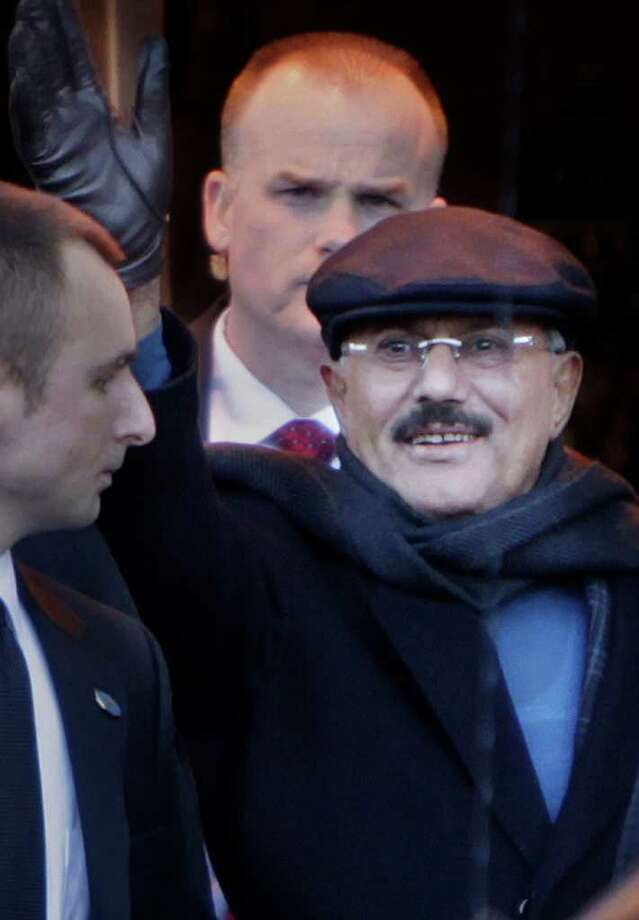 Yemeni President Ali Abdullah Saleh waves to people protesting his presence in the United States as he exits his hotel in New York, Sunday, Feb. 5, 2012. Saleh arrived in the United States on Saturday, Jan. 28, 2012,  for treatment of burns he suffered during an assassination attempt in June. Human Rights Watch, a New York-based human rights organization says it has documented the deaths of hundreds of anti-government protesters in confrontations with Saleh's security forces,  and while they are not opposed to Saleh receiving care in the United States, the organization wants assurances that concerned governments will insist on prosecution for those responsible for last year's attacks. (AP Photo/Seth Wenig) Photo: Seth Wenig