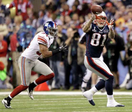 New England Patriots tight end Aaron Hernandez (81) looks to catch a pass against New York Giants safety Deon Grant (34) during the first half of the NFL Super Bowl XLVI football game, Sunday, Feb. 5, 2012, in Indianapolis. (AP Photo/Marcio Jose Sanchez) Photo: Marcio Jose Sanchez, Associated Press / AP