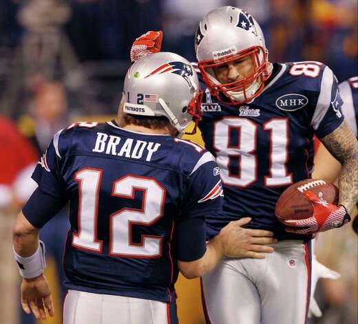 New England Patriots quarterback Tom Brady (12) congratulates tight end Aaron Hernandez (81) on his touchdown reception during the second half of the NFL Super Bowl XLVI football game against the New York Giants, Sunday, Feb. 5, 2012, in Indianapolis. (AP Photo/Paul Sancya) Photo: Paul Sancya, Associated Press / AP
