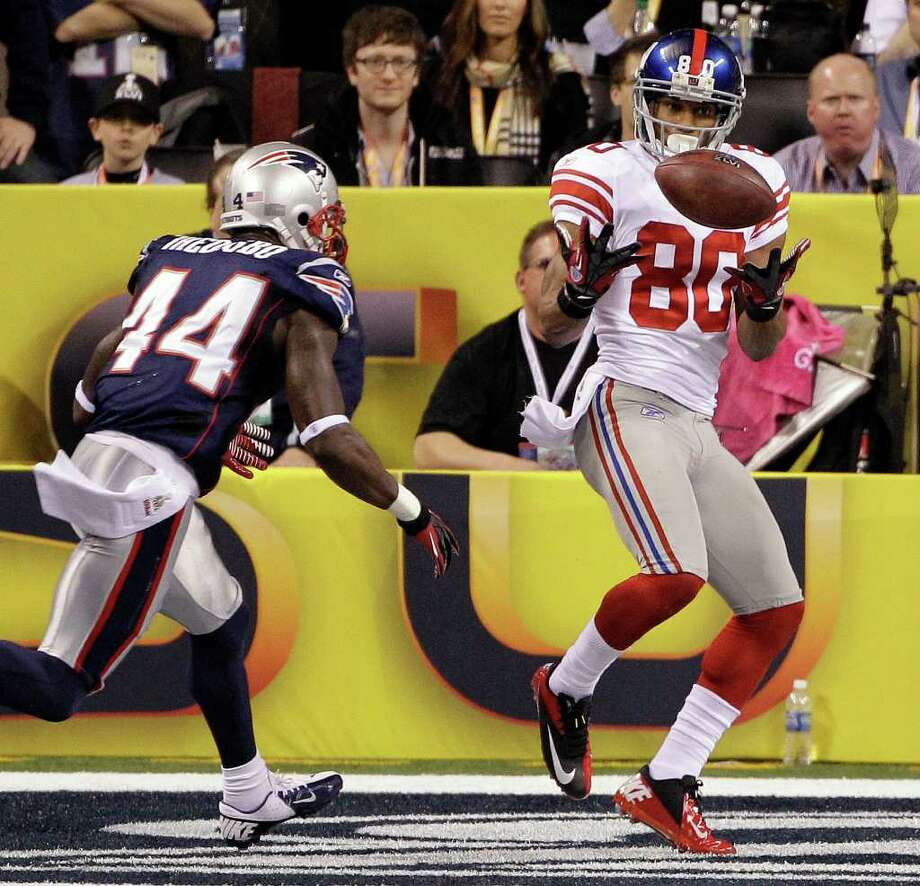Giants wide receiver Victor Cruz catches a touchdown pass in front of Patriots safety James Ihedigbo. Photo: AP