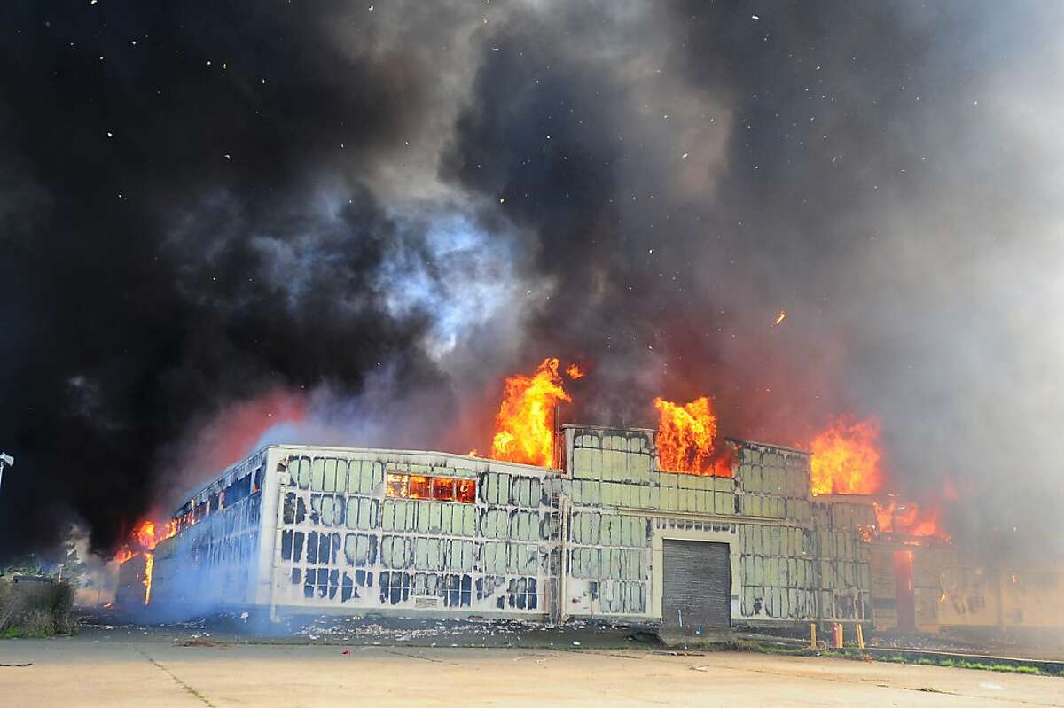 Debri rains down as building 655 on the North end of Mare Island burns during a 4-alarm fire on Sunday in Vallejo. (Chris Riley/Times-Herald)