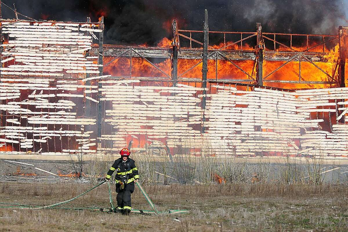A Vallejo firefighter pulls a hose away from a hot burning 4-alarm fire at building 655 on Mare Island. Water is scarce in this area making it difficult for firefighters to get the blaze under control.(Chris Riley/Times-Herald)
