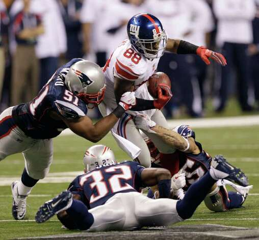 New York Giants wide receiver Hakeem Nicks (88) fumbles the ball as he is hit by New England Patriots linebacker Jerod Mayo (51) and cornerback Devin McCourty (32) during the second half of the NFL Super Bowl XLVI football game Sunday, Feb. 5, 2012, in Indianapolis.  Nicks recovered the ball. (AP Photo/David J. Phillip) Photo: David J. Phillip, Associated Press / AP