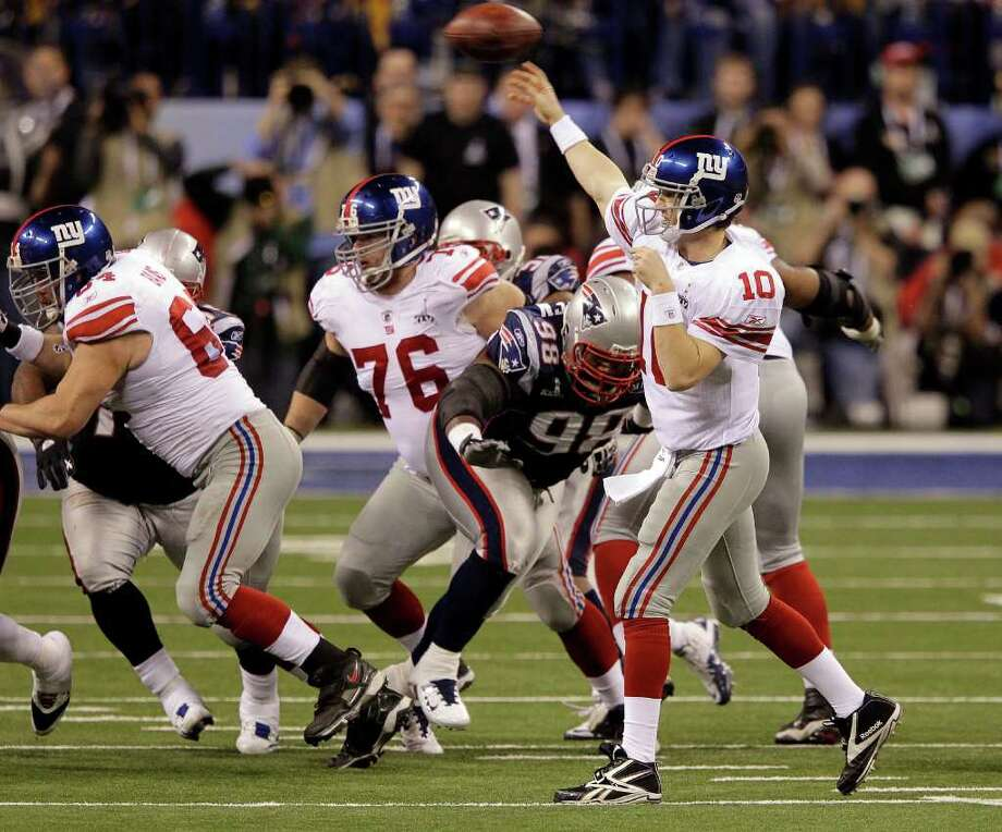 New York Giants quarterback Eli Manning throws a pass as New England Patriots defensive lineman Gerard Warren rushes during the second half of the NFL Super Bowl XLVI football game, Sunday, Feb. 5, 2012, in Indianapolis. (AP Photo/Michael Conroy) Photo: Michael Conroy