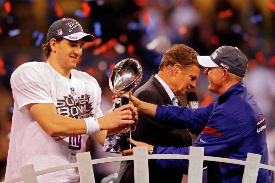 INDIANAPOLIS, IN - FEBRUARY 05:  Eli Manning #10 of the New York Giants poses with the Vince Lombardi Trophy and his head coach Tom Coughlin after the Giants defeated the Patriots by a score of 21-17 in Super Bowl XLVI at Lucas Oil Stadium on February 5, 2012 in Indianapolis, Indiana. Photo: Rob Carr, Getty Images / 2012 Getty Images