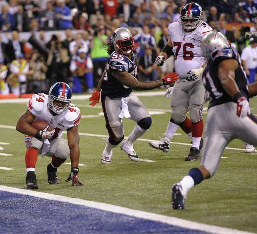 Ahmad Bradshaw (L) of the New York Giants scores the game-winning touchown late in the fourth quarter against the New England Patriots during Super Bowl XLVI on February 5, 2012 at Lucas Oil Stadium in Indianapolis, Indiana.  Bradshaw ran six yards for the deciding touchdown with 57 seconds remaining to give the Giants a 21-17 victory over the Patriots in Super Bowl 46.   It was the fourth Super Bowl triumph for the Giants, who also defeated the Patriots in the 2008 NFL championship spectacle and captured the crown in 1987 and 1991.  AFP PHOTO / TIMOTHY A. CLARYChasev Photo: TIMOTHY A. CLARY, AFP/Getty Images / AFP