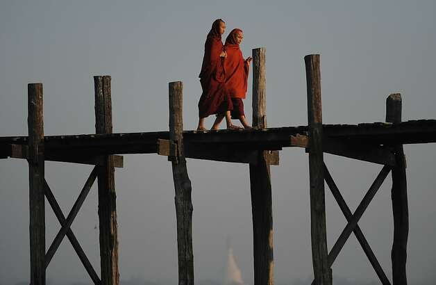 Buddhist monks walk on the U Bein's bridge as they cross the Taungthaman lake in Amarapura, Myanmar's penultimate royal capital located 10 kms south of Mandalay in the north of the country, early on February 5, 2012.  The world's longest teak footbridge curves some 1,300 metres across the lake, connecting the two sides of the ancient capital. Myanmar is emerging from political and economic isolation after decades of military rule since a nominally civilian government took power last year. With the West looking at easing sanctions and businesses closely watching sweeping democratic reforms in the country, Myanmar needs to prepare for an anticipated increase in investments and tourism, analysts said.   AFP PHOTO/Christophe ARCHAMBAULT (Photo credit should read CHRISTOPHE ARCHAMBAULT/AFP/Getty Images) Photo: Christophe Archambault, AFP/Getty Images