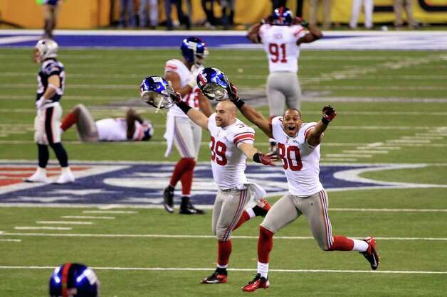 INDIANAPOLIS, IN - FEBRUARY 05:  Tyler Sash #39 and Victor Cruz #80 of the New York Giants celebrate on the field after defeating the New England Patriots in Super Bowl XLVI at Lucas Oil Stadium on February 5, 2012 in Indianapolis, Indiana. The New York Giants defeated the New England Patriots 21-17. Photo: Chris Trotman, Getty Images / 2012 Getty Images