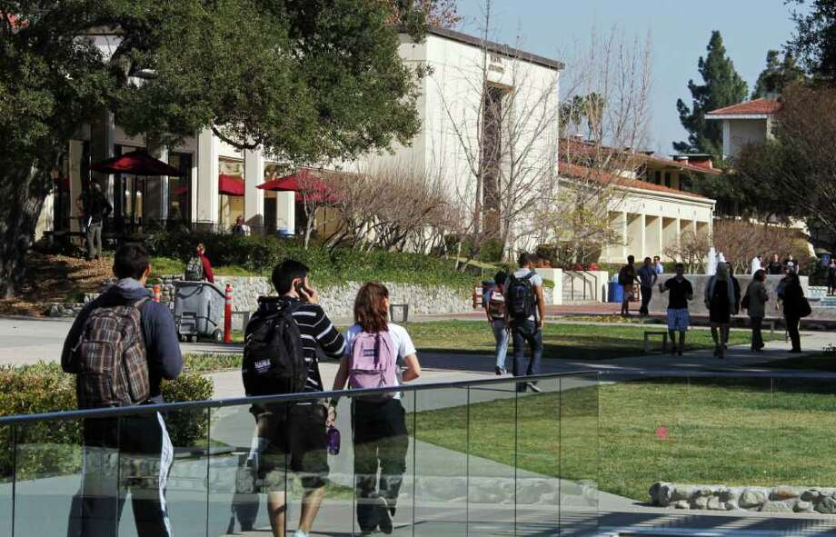 "In this Thursday, Feb. 2, 2012 photo, students walk through the campus of Claremont McKenna College in Claremont, Calif. When US News & World Report debuted its list of ""America's Best Colleges"" nearly 30 years ago, the magazine hoped its college rankings would be a game-changer for students and families. Arguably, they've had a much bigger effect on colleges themselves. A senior administrator at Claremont McKenna, a highly regarded California liberal arts college, resigned after acknowledging he falsified college entrance exam scores for years to rankings publications such as US News. The scale was small: submitting scores just 10 or 20 points higher on the 1600-point SAT math and reading exams. (AP Photo/Reed Saxon) Photo: Reed Saxon"