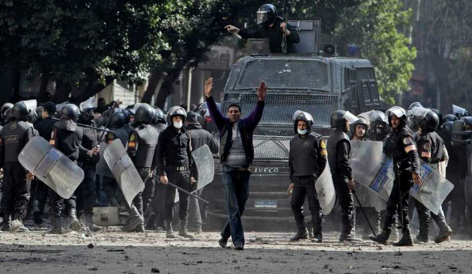 An Egyptian man, center, gestures to protestors asking them to stop throwing stones at security forces during clashes near the Interior Ministry in Cairo, Egypt, Sunday, Feb. 5, 2012. Volleys of tear gas left a white cloud over Cairo's Tahrir Square and surrounding streets in the vicinity of Egypt's Interior Ministry, in the fourth day of clashes between security forces and rock-throwing youth protesting a deadly soccer riot. (AP Photo/Muhammed Muheisen) Photo: Muhammed Muheisen / AP