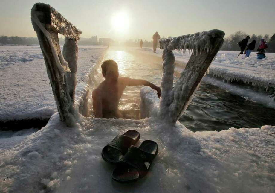 A Russian man climbs out from an ice hole after swimming in a lake on the outskirts of St.Petersburg, Russia, Sunday, Feb. 5, 2012. The temperature in St.Petersburg hit -23 Celsius (-9.4Fahrenheit).  (AP Photo/Dmitry Lovetsky) Photo: Dmitry Lovetsky