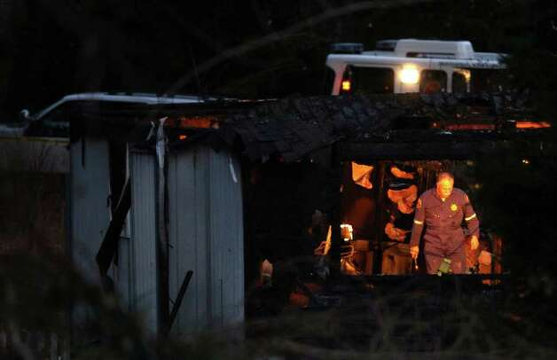 An investigator works in the home of Josh Powell after the home burned, killing Powell and his two sons Charlie and Braden in unincorporated Pierce County on Sunday, February 5, 2012. Powell has been a person of interest in the disappearance of his wife, Susan Cox Powell. Sheriff Paul Pastor said he was certain that Josh Powell burned the house, killing himself and the two boys. Photo: JOSHUA TRUJILLO / SEATTLEPI.COM