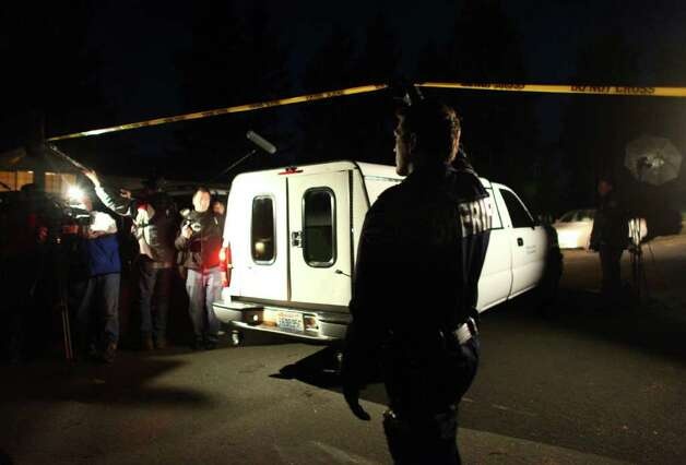 A Sheriff's deputy lifts crime scene tape for a truck holding bodies removed from the home of Josh Powell after Powell reportedly burned down the house, killing his two sons Charlie and Braden, in unincorporated Pierce County on Sunday, February 5, 2012. Powell has been a person of interest in the disappearance of his wife, Susan Cox Powell. Sheriff Paul Pastor said he was certain that Josh Powell burned the house, killing himself and the two boys. Photo: JOSHUA TRUJILLO / SEATTLEPI.COM