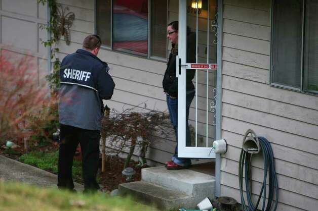 An investigator interviews a neighbor near the home of Josh Powell after Powell reportedly burned down the house in unincorporated Pierce County on Sunday, February 5, 2012. Powell has been a person of interest in the disappearance of his wife, Susan Cox Powell. Sheriff Paul Pastor said he was certain that Josh Powell burned the house, killing himself and his two boys Charlie and Braden. Photo: JOSHUA TRUJILLO / SEATTLEPI.COM
