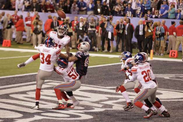 The Hail Mary pass on the final play gives the Giants a brief scare before falling out of the reach of the Patriots' Rob Gronkowski. Photo: Michael Conroy / AP