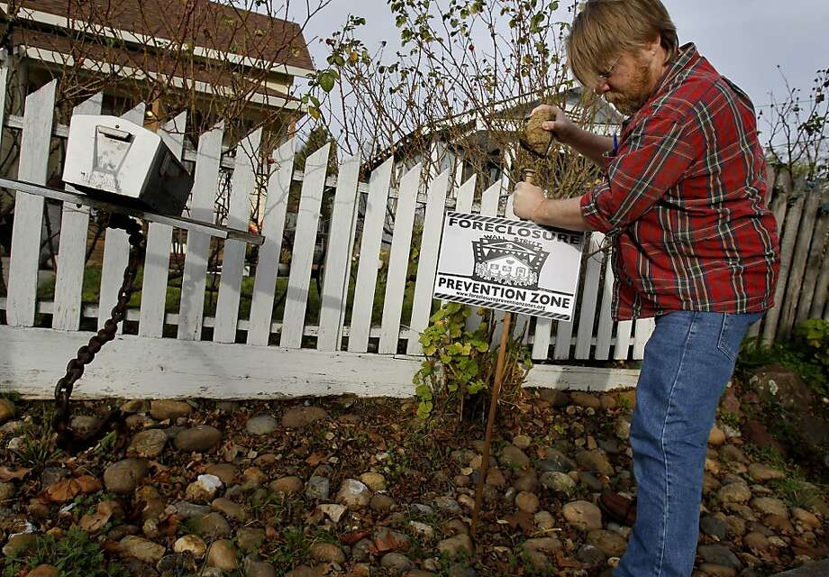Tim Nonn, an Occupy Petaluma member who lost his home to foreclosure earlier, plants a sign at a neighbors home. In Petaluma, Calif. members of the local Occupy group have taken on a completely different agenda then the more confrontational urban groups in the Bay Area.  Occupy Petaluma is concentrating on local foreclosures and trying to counsel homeowners in trouble. Photo: Brant Ward, The Chronicle