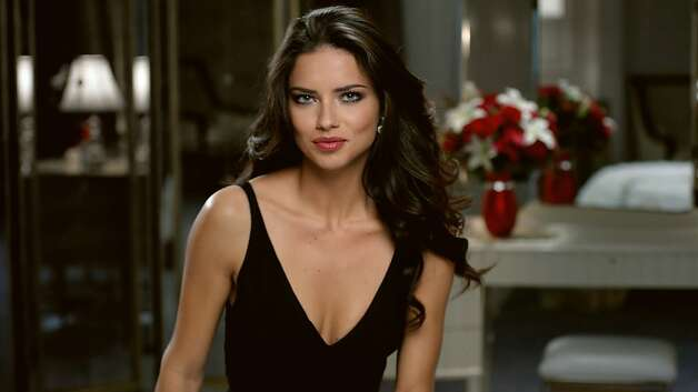 This advertisement provided by Teleflora, shows a scene from the ad with super-model Adriana Lima set to launch during Super Bowl XLVI, which will air Sunday, Feb. 5, 2012. Teleflora's 30-second spot will debut during the game's second quarter. About 20 of the roughly 36 Super Bowl advertisers put their TV commercials online in the days leading up to Sunday's broadcast. That's a big break with tradition and up from last year when only a handful of companies released their ads before the game. Millions have already viewed Lima's pre-released Teleflora ad. (AP Photo/Telaflora) Photo: Associated Press